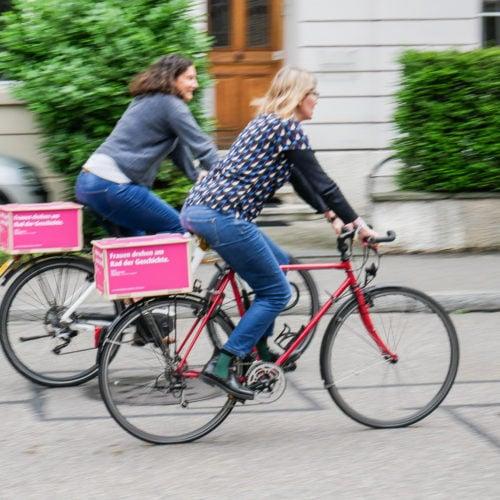 Zwei Fahrradfahrerinnen mit Werbung für den Frauenstreik.