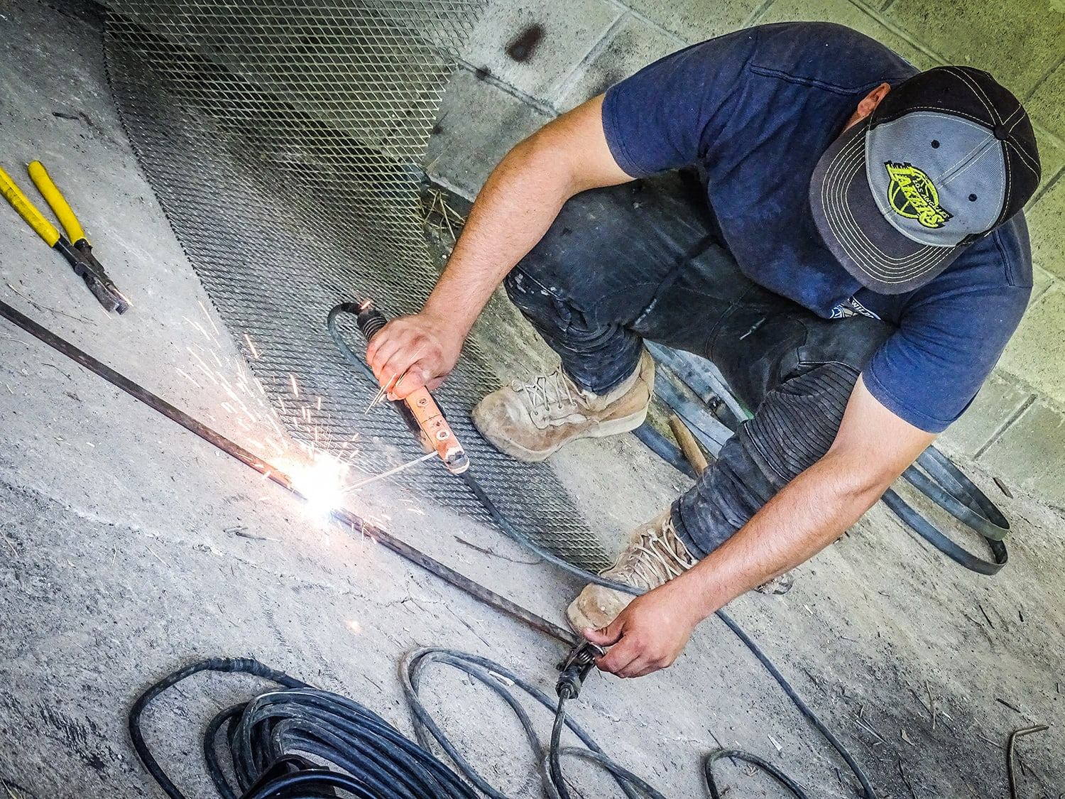 A young man squatting, welding a piece of metal.