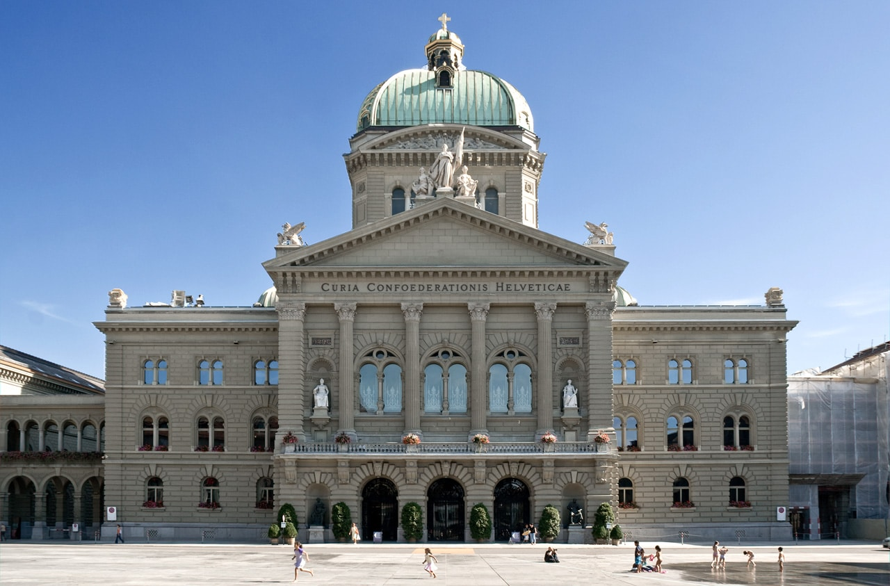 The Bundeshaus in Bern under a cloudless sky. People on the Bundesplatz.
