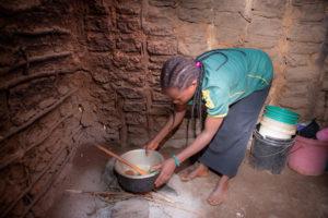 Aronia stellt einen Topf auf die kleine Feuerstelle in ihrer Hütte.