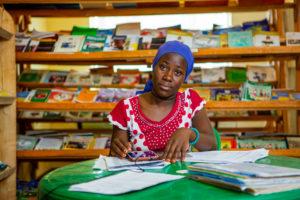Aronia sitzt an einem grünen Plastiktisch vor einem Stapel Papiere. Im Hintergrund Holzregale mit Zeitschriften.