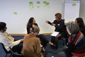 Gesprächsgruppe diskutiert in einer Runde. Wand mit Notizzettel im Hintergrund.