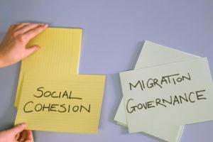 """Weisse Wand mit gelben und grünen Zetteln auf denen steht """"Social Cohesion"""" und """"Migration Governance""""."""