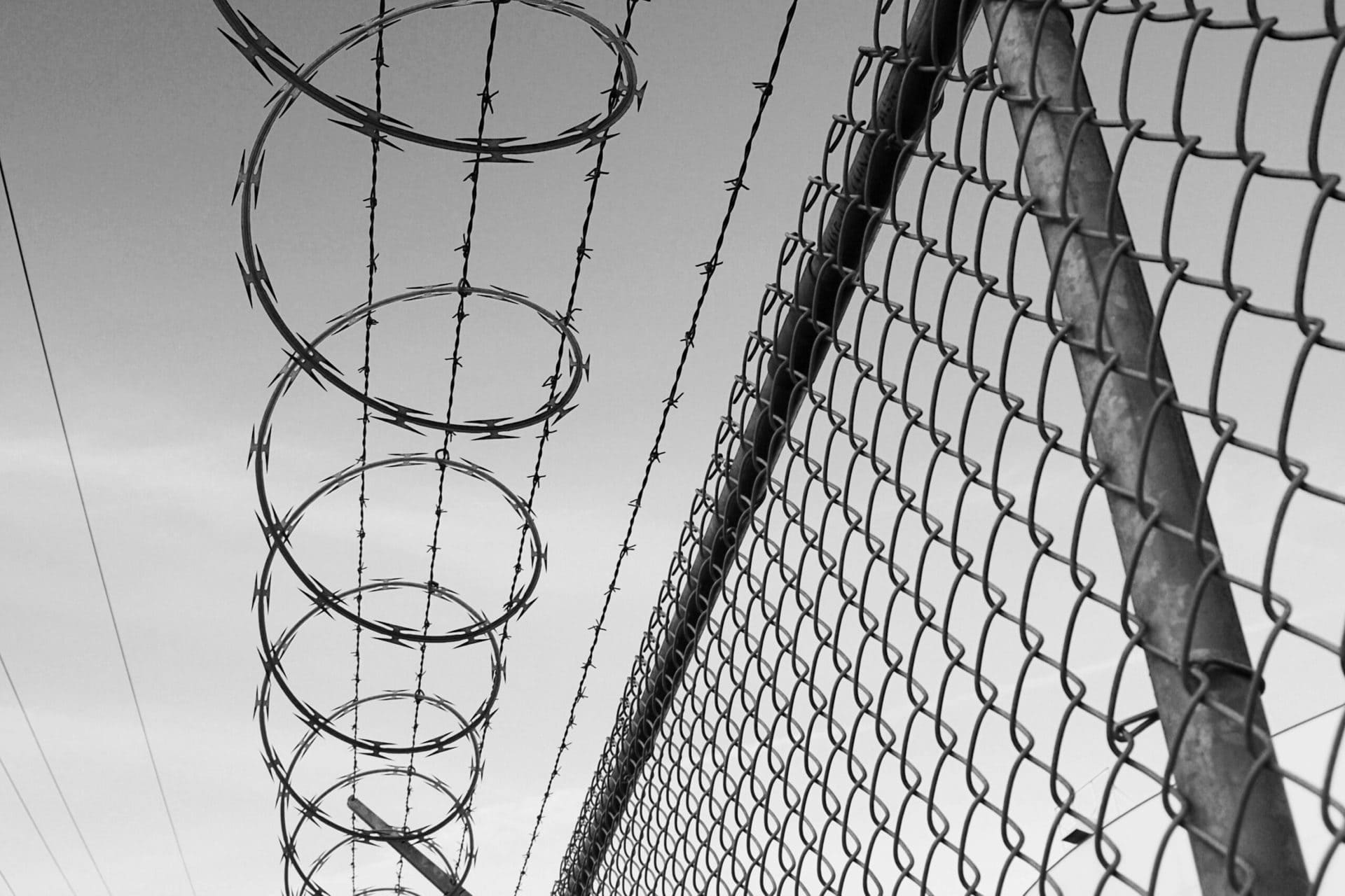 Barbed wire and wire fence black and white with sky