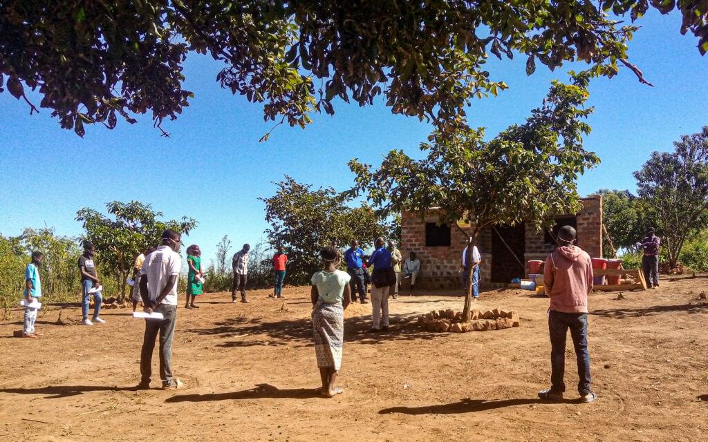Jugendliche stehen mit Abstand im Kreis auf Schotterboden