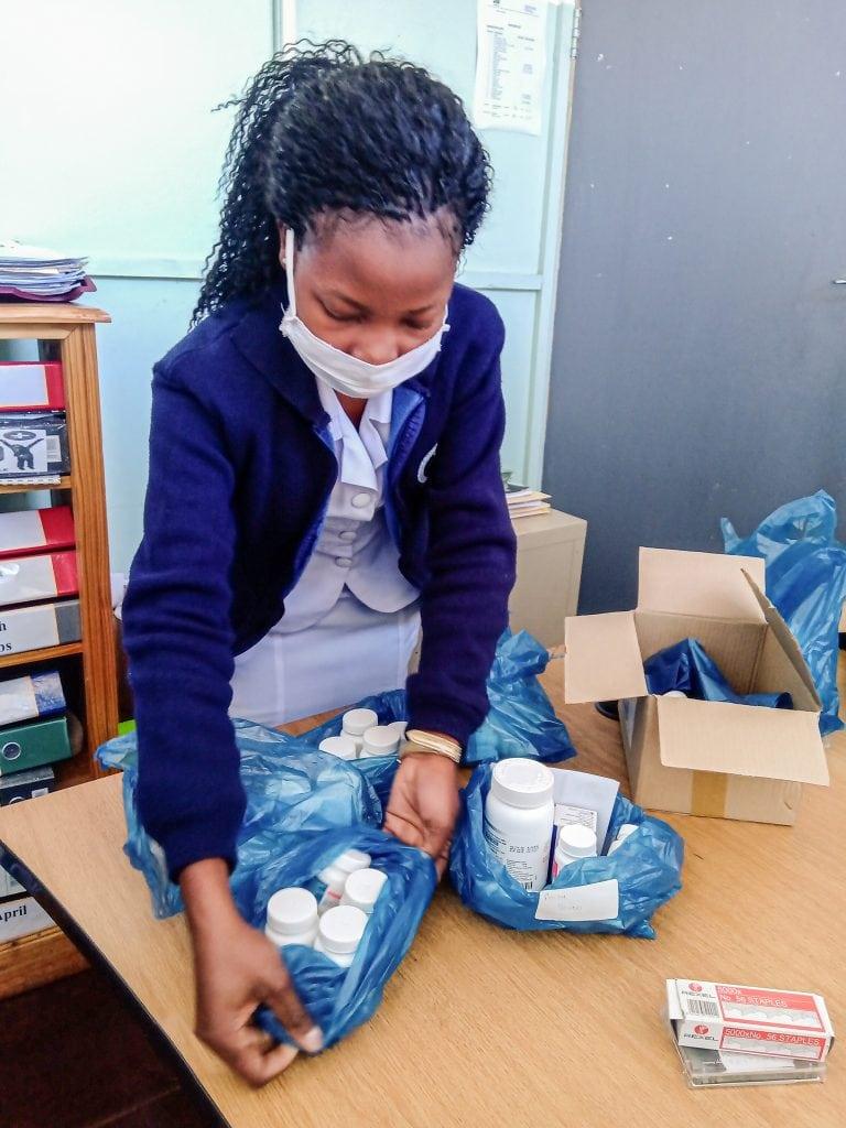 Schwarze Frau mit Mundschutz packt Medizin in blaue Plastikbeutel.