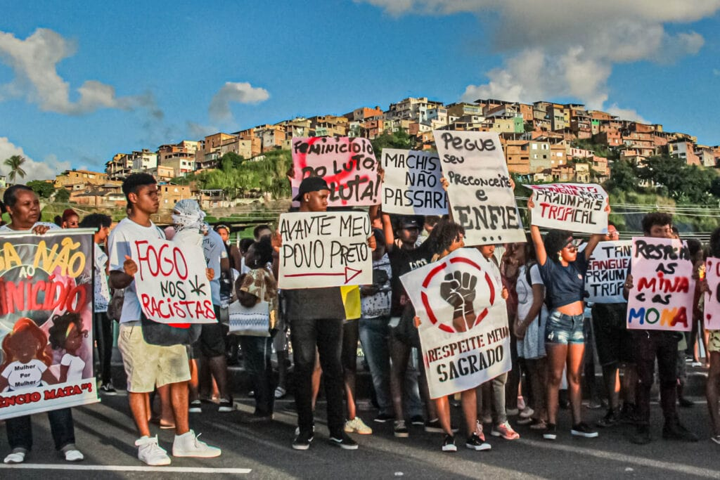 Junge Menschen halten Anti-Waffen-Schilde hoch, portugiesische Sprüche