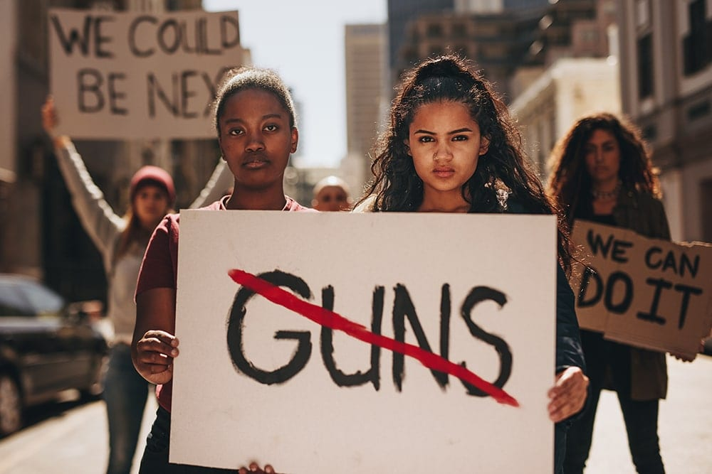 "Girls hold sign ""Guns"" crossed out"