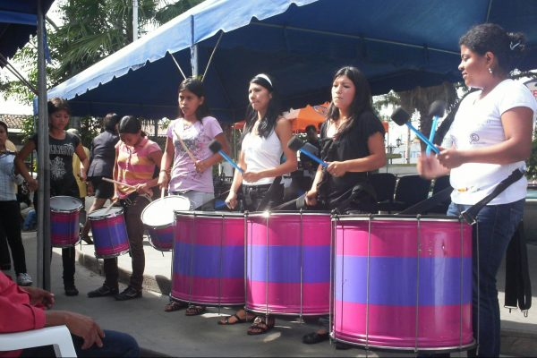 Junge Frauen von Las Melidas schlagen auf grossen Trommeln an einer öffentlichen Kundgebung.