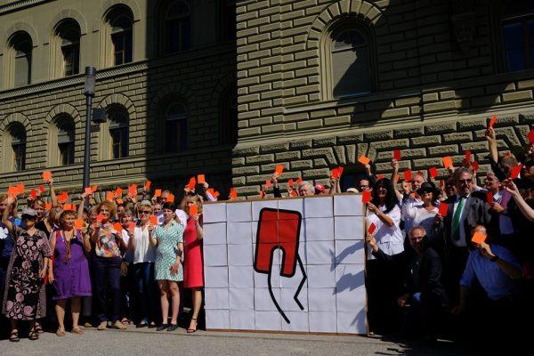 Menschen vor dem Bundeshaus zeigen rote Karte.