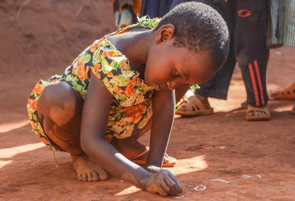 Ein Mädchen aus Tansania schreibt mit weisser Kreide auf den Lehmboden.