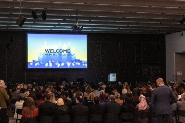 Leinwand mit Beamerbild: Welcome to the Basel Peace Forum. Publikum im abgedunkelten Saal.