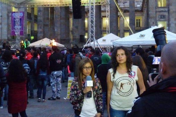 Eine junge Frau von ACOOC wird im Juli 2014 an einem Anti-Militär-Festival in Bogota vom lokalen Fernsehsender Canal Capital interviewt. Im Hintergrund ist eine Bühne zu sehen.