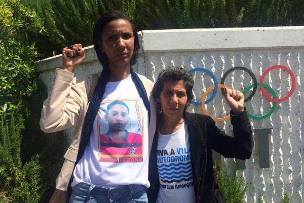 Ana Paula Gomes de Oliveira mit ihrer erhobenen Faust vor dem Gebäude der UNO. Hinter iher die Fahnen der Mitgliederländer.