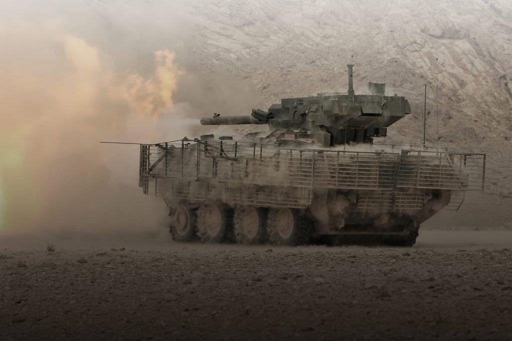 Panzer, der im Staub eine Salve abfeuert
