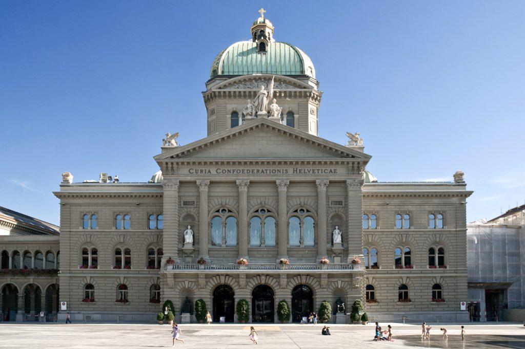 Das Bundeshaus in Bern bei wolkenlosem Himmel. Menschen auf dem Bundesplatz.