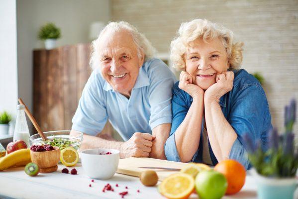 Eine ältere Frau und ein älterer Mann die fröhlich in die Kamera blicken.