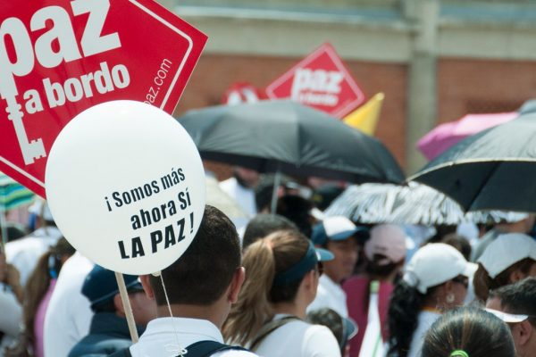 Many people hold red signs with the white inscription