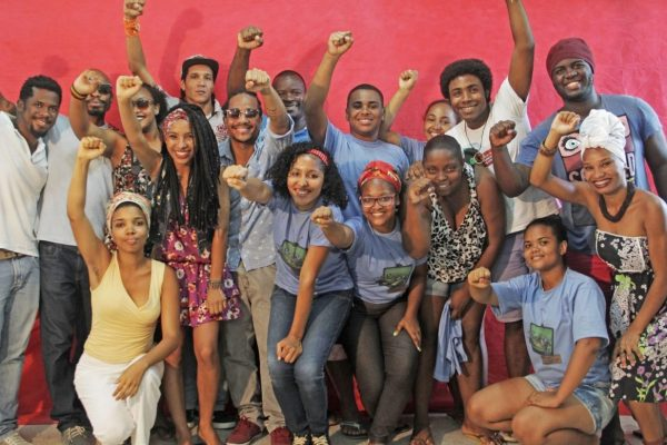 A group picture with young people in front of a red wall.