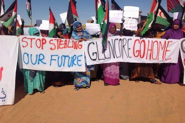 Sahraouis demonstrieren mit Transparenten: Glencore go home!
