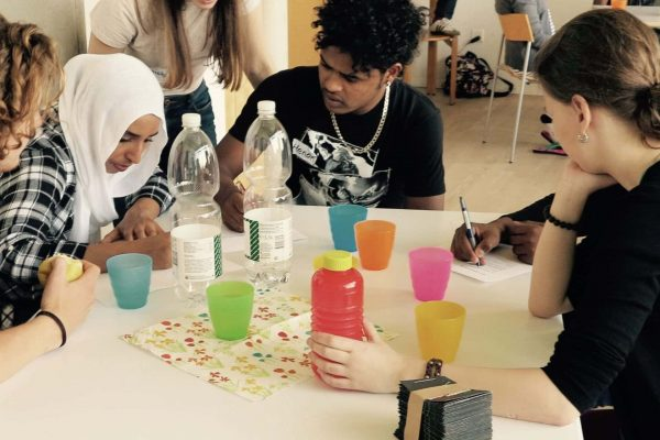 Jugendliche sitzen arbeitend zusammen an einem Tisch.