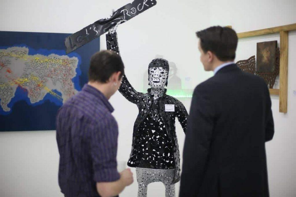 Zwei Besucher betrachten eine lebensgrosse Figur aus Metall mit einem Schild in der Hand. Text: Let's Rock!