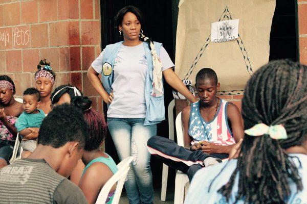 Eine Mitarbeiterin zusammen mit Jugendlichen.