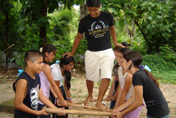 Ein Jugendlicher läuft auf drei Holzstangen, die von anderen sechs Jugendlichen gehalten werden.