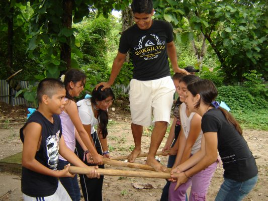 One teenager walks on three wooden poles, which are held by other six teenagers.