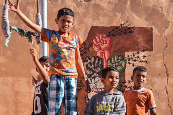Vier Jungs vor einer Lehmwand mit politischen Gafitti.