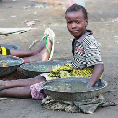 Mädchen rührt mit ihrer Hand in einer Brühe aus flüssigem Quecksilber und anderen Chemikalien um das Gold auszuwaschen..