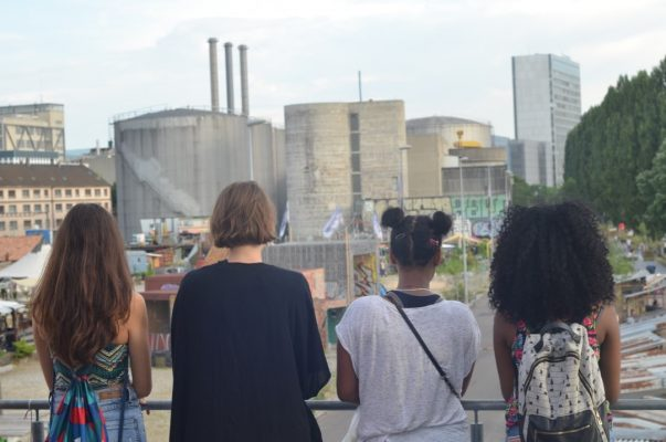 Young people look with their backs to the camera into the distance at the wooden park on the Klybeck area.