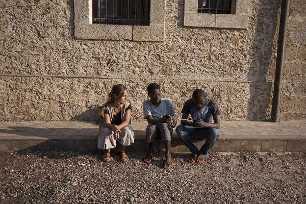 A woman sitting with two black boys on the pavement in front of a stonewall.
