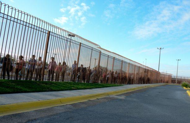 Eine lange Schlange entlang eines Grenzzauns zwischen den USA und Mexiko.