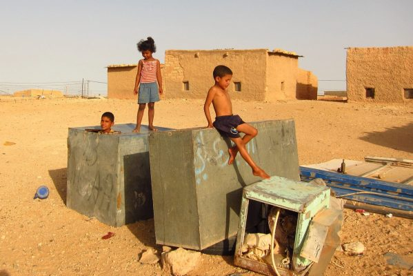 Children climb around on old, rusty metal boxes that lie in the refugee camp in the desert.