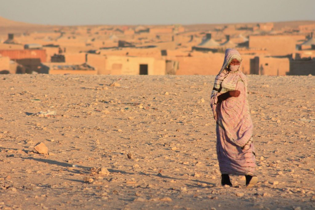 Junge Frau im Vordergrund, Lager im Hintergrund.