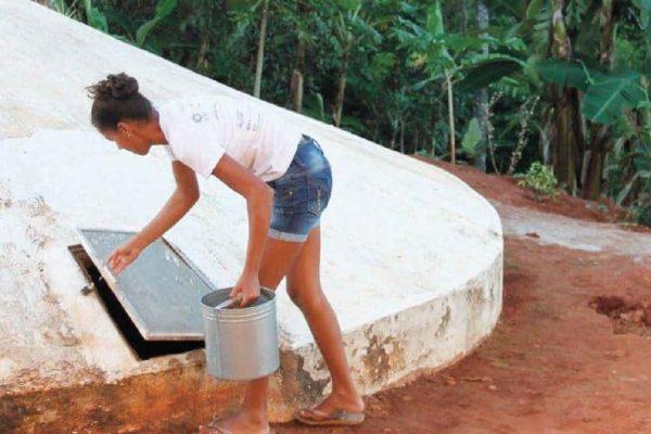 Eine junge Frau holt Wasser aus einer weissen